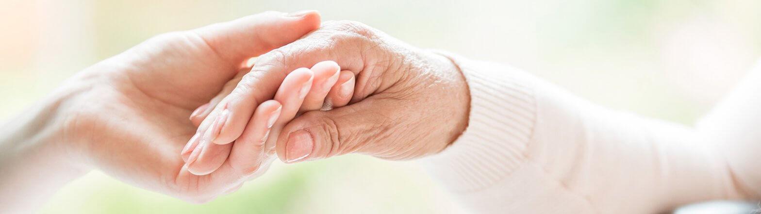 Pflegerin hält Hand von Seniorin in Essen
